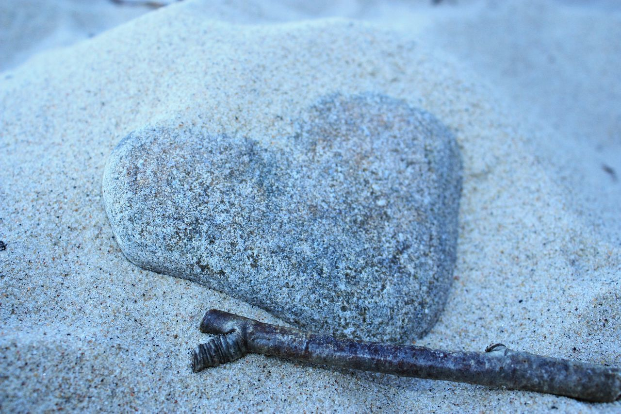 Close-Up Of Stick By Heart Shape Stone At Beach