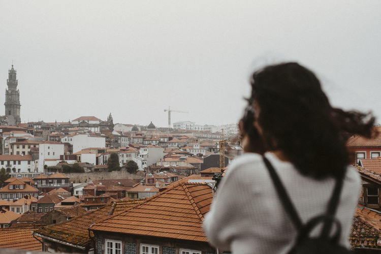 Rear view of young woman with backpack photographing cityscape against sky