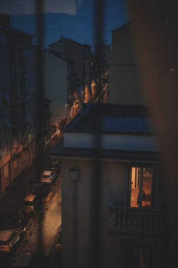 Illuminated street by buildings in city at night