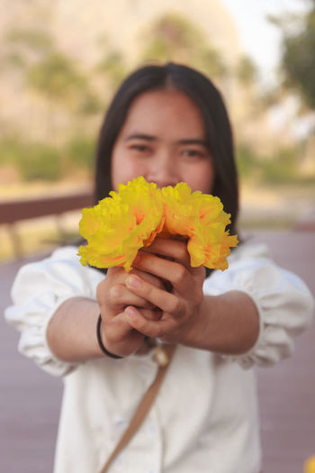 Close-up of woman holding yellow flower