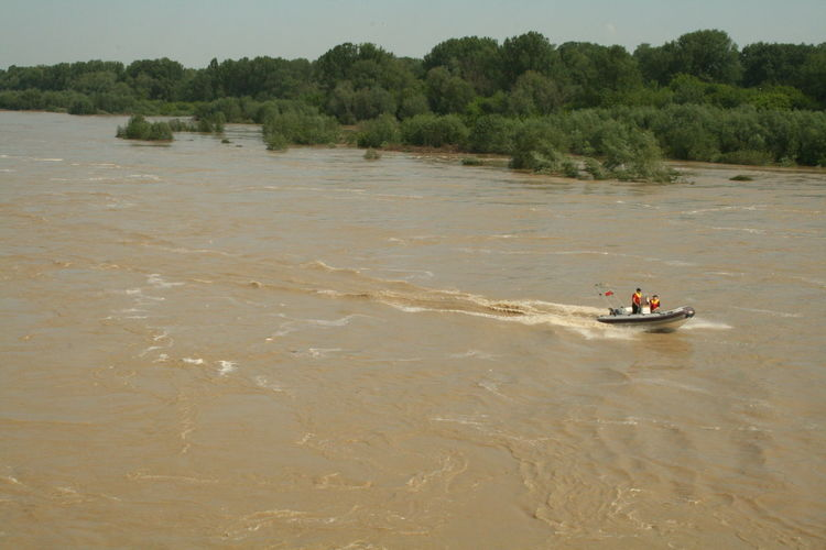 Two people sailing in a motorboat on river