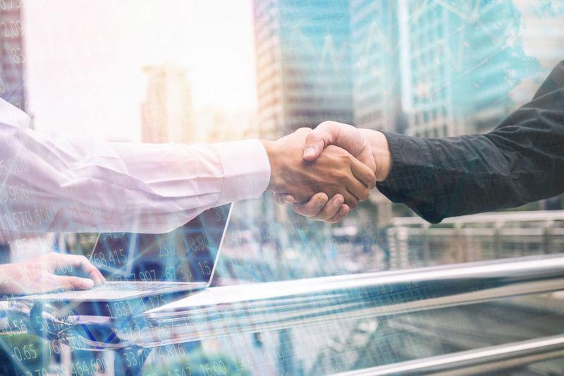 Digital Composite Image Of Business People Giving Handshake Against Buildings In City