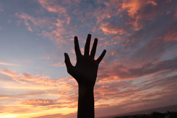 Low angle view of silhouette hand against orange sky