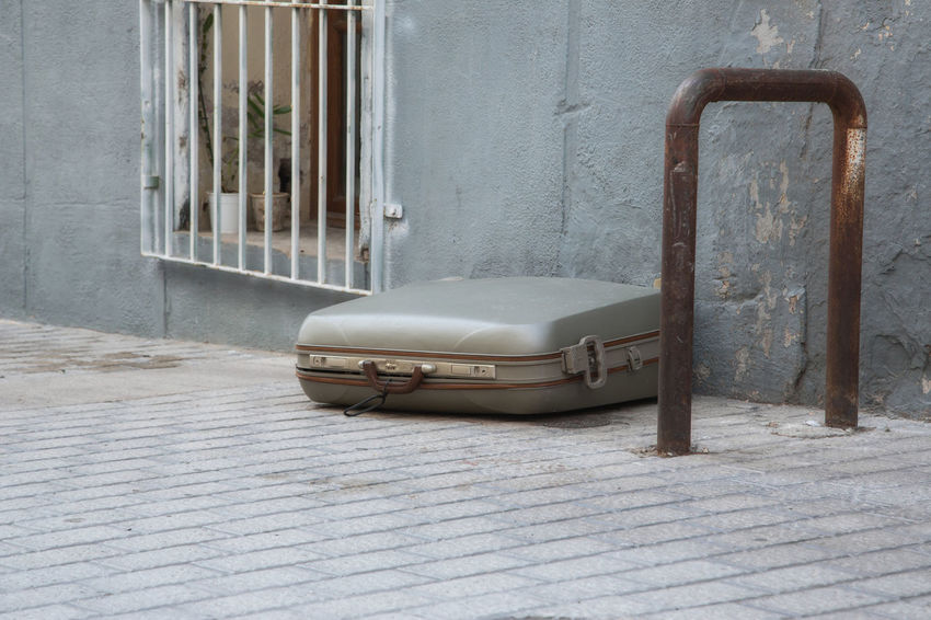 A suitcase lying alone on the street Alone Forgotten Holiday Travel Architecture Bag Building Exterior Built Structure Case Close-up Day No People Outdoors Street Suitcase Trunk
