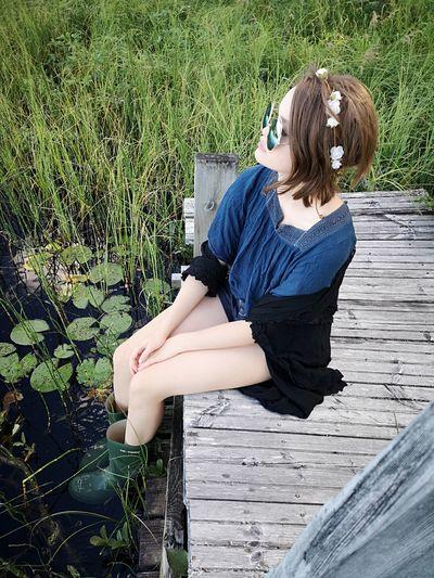 Girl Sitting On Pier Over Lake