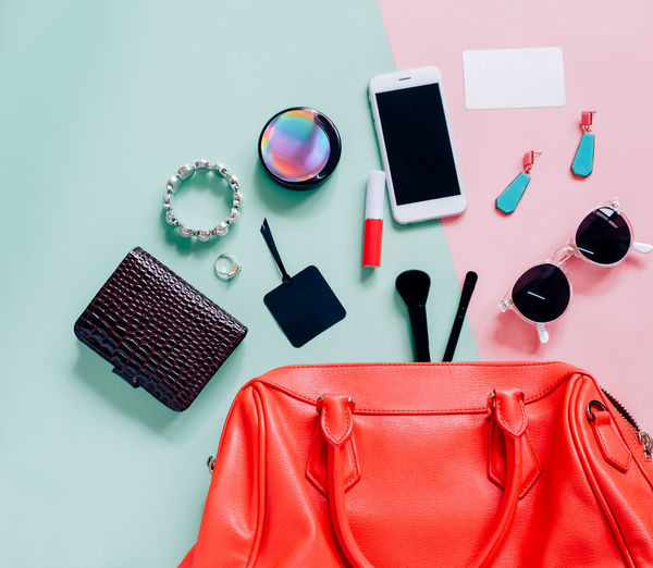 Directly above shot of smart phone with beauty products on table