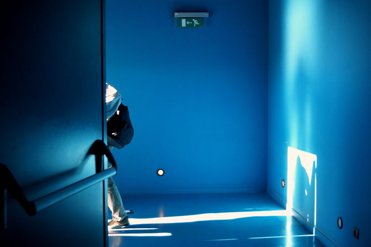 A man leaving an indoors cinema hall from the emergency exit. Bag Blue Blue Color Close-up Day Emergency Emergency Exit Escape Escape Way Exit Exit Sign Indoors  One Person Shadow Signage Signs