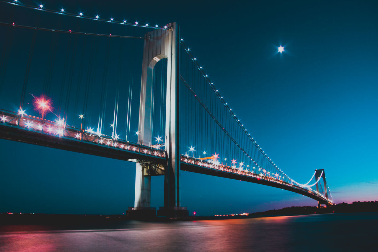 illuminated, night, bridge - man made structure, connection, architecture, suspension bridge, built structure, travel destinations, lighting equipment, outdoors, transportation, travel, low angle view, waterfront, water, sky, no people, chain bridge