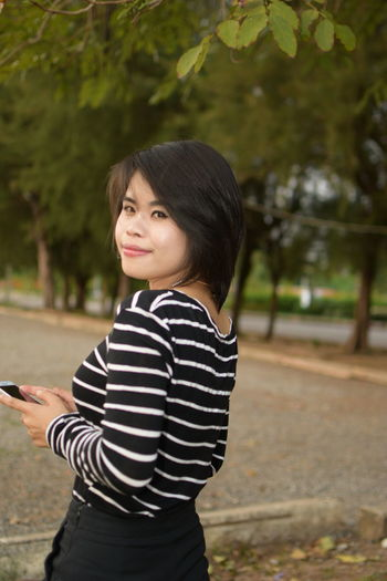 Casual Clothing Focus On Foreground Hairstyle Lifestyles Looking Mobile Phone Nature One Person Outdoors Plant Real People Side View Standing Striped Technology Three Quarter Length Tree Waist Up Wireless Technology Women Young Adult