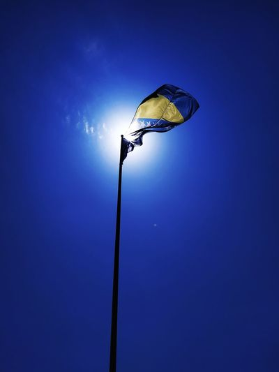 Low angle view of flag waving against clear blue sky during sunny day