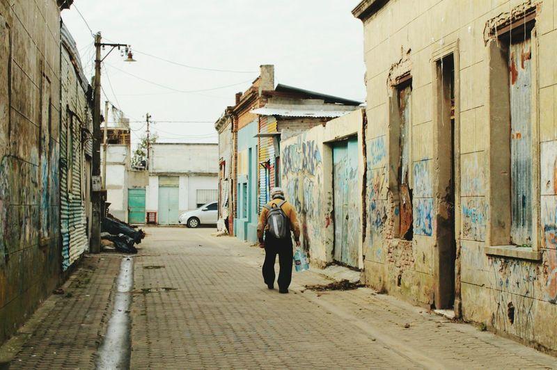 Rear view of man walking on cobblestone street