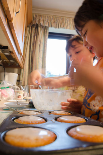 Young brothers decorating home made angel cakes. Cakes Cupcakes Fattening Icing Baked Baking Bowl Boys Childhood Domestic Life Elementary Age Food Food And Drink Freshness Home Interior Leisure Activity Lifestyles Preparation  Real People Sweet Table Taste Tasty Togetherness Unhealthy