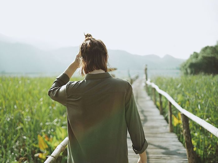 Rear view of woman standing on boardwalk amidst agricultural field