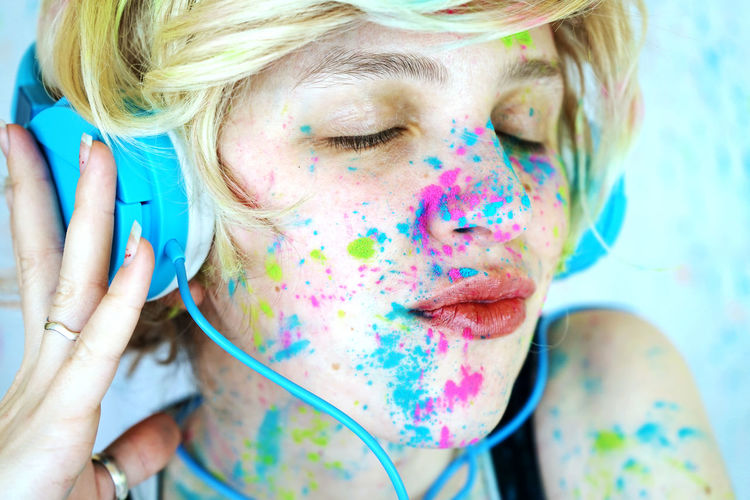 Close-Up Of Woman With Powder Paint On Her Face Listening Music