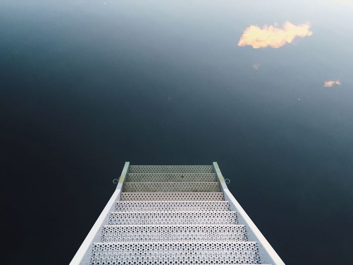 High Angle View Of Ladder Leading Towards Calm Lake
