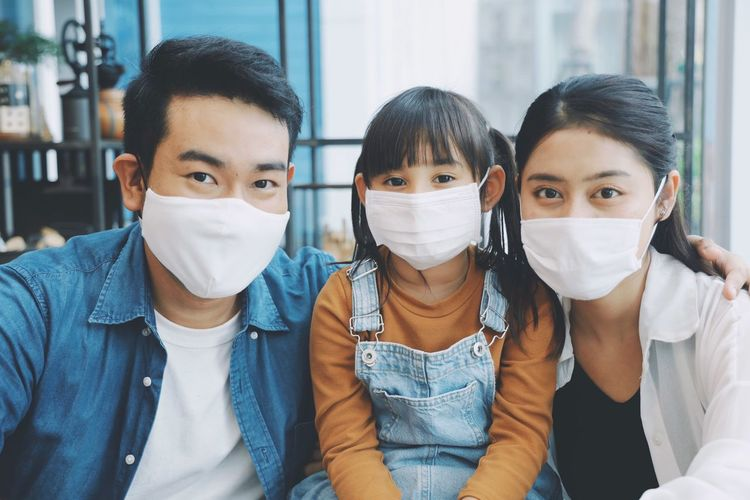 Portrait of smiling family wearing flu mask sitting at home