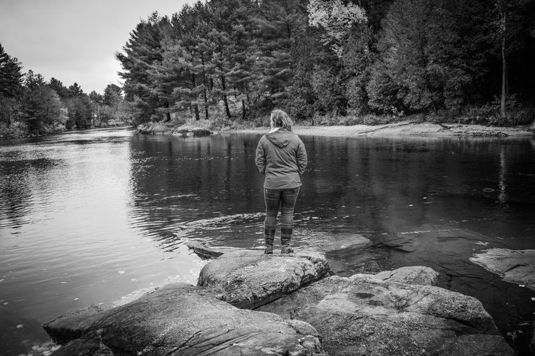 Rear view of woman standing on rock by lake