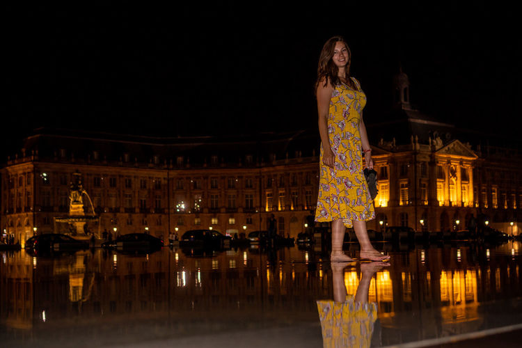 Low angle view of woman standing on floor against illuminated building at night