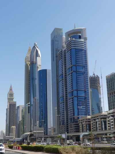 Skyscrapers on Sheik Zayed Road, Dubai, United Arab Emirates 2019 Dubai UAE 2019 Sheik Zayed Road Blue Sky Sunlight And Shade No People Low Angle View Skyscrapers Tower Blocks Tall - High City Urban Skyline Cityscape Financial District  Modern Design Modern Architecture Steel And Glass Structures Metro Track Architecture Modern Travel Destinations Building Exteriors Road Vehicles On Road