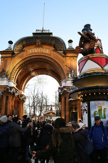 Tivoli Tivoli Tivoli Denmark Tivoli Garden Architecture Art And Craft Building Exterior Built Structure Carousel Crowd Day Human Representation Large Group Of People Lifestyles Low Angle View Male Likeness Men Outdoors People Real People Sculpture Sky Statue Tree Women