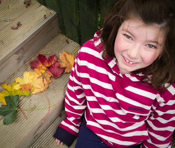 Girl Looking At Camera From Above  Eyes Face HEAD One Child One Person Stripy Jumper Outdoors Sitting Wooden Decking Day Leaves Rainbow Colours Autumn Collection Fence Wood - Material Red And White Colour Image Childhood One Girl Real People