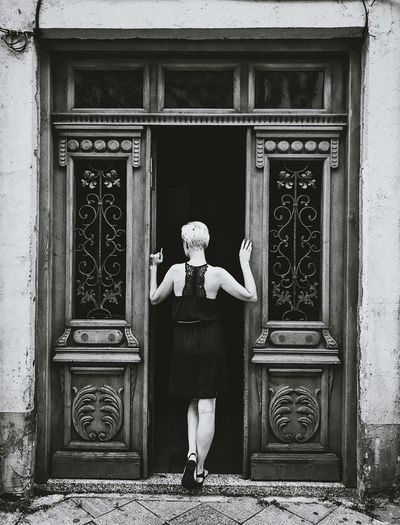 Rear view of woman standing against closed door of building