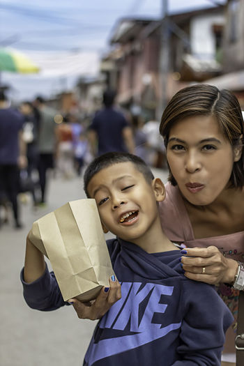 Mother and son eat candy on the street and blurry tourists at Walking Street Chiang Khan, Loei in Thailand. Child Childhood Incidental People Women Focus On Foreground Females Real People Girls Happiness Portrait Two People Lifestyles Smiling Togetherness Front View Looking At Camera City Family Leisure Activity Sister Innocence