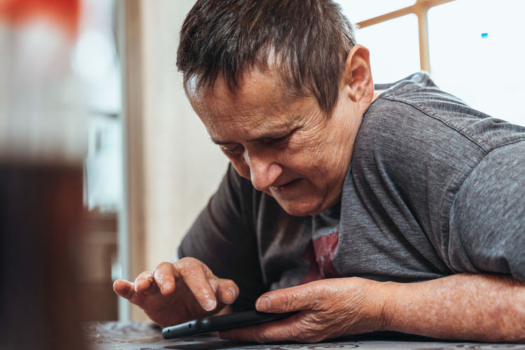 Close-up of man using phone while sitting at home