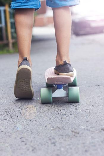 Low section of boy skateboarding on street