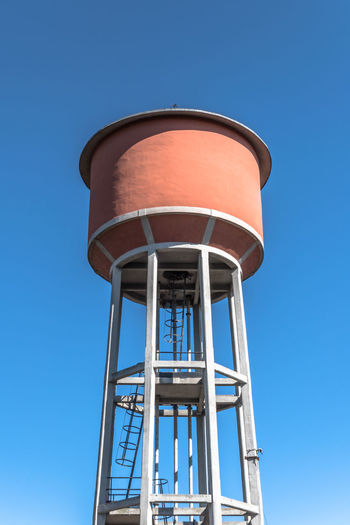 Low angle view of water tower against blue sky