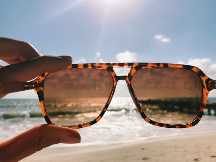 Close-up of human hand holding sunglasses at beach against sky during sunny day