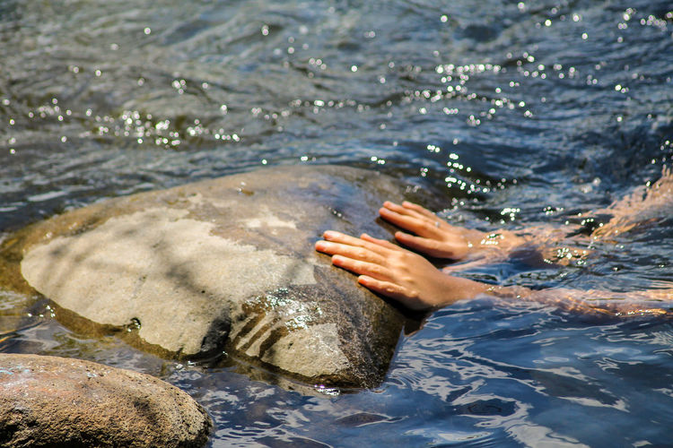 Close up of hands coming out from under water