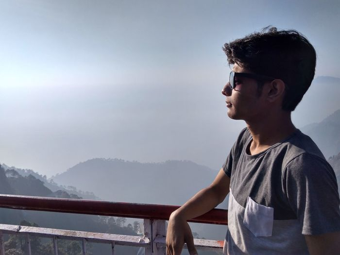 Young Man Wearing Sunglasses While Looking At View Against Sky