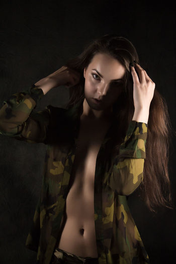 Adult Arms Raised Beautiful Woman Beauty Black Background Contemplation Dark Fashion Front View Hair Hairstyle Hand In Hair Human Arm Indoors  Long Hair Looking At Camera One Person Portrait Studio Shot Women Young Adult Young Women