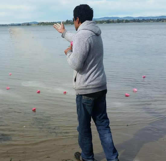 Rear View Of Man Throwing Sand In Sea