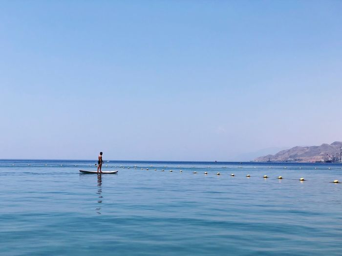 Man paddleboarding in sea against clear blue sky