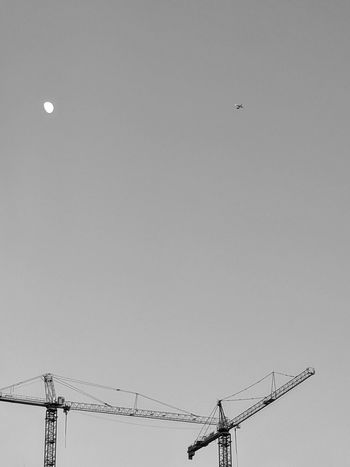 I see the moon a plane Sky and a few construction cranes Adventures In The City