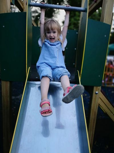 Cute Girl Playing On Slide On Playground