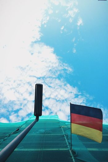 Low Angle View Of German Flag On Construction Building Against Sky
