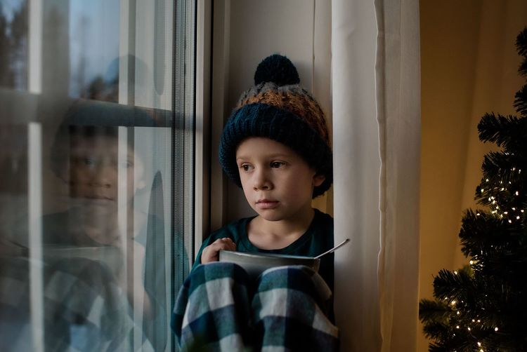 Portrait of boy looking through window at home