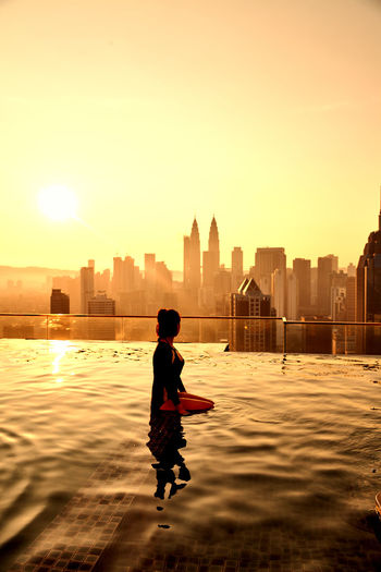 Woman Standing In Infinity Pool Against Cityscape