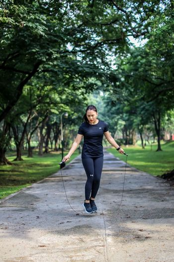 Woman Jumping With Rope On Footpath Against Trees