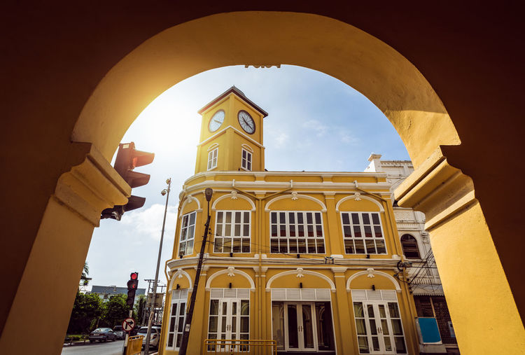 Chino portuguese style clock tower in phuket, Thailand. Architecture Building Exterior Built Structure Arch Sky Building Low Angle View Yellow No People Day Window City Nature Spirituality Outdoors Tower Colonial Architecture Chino Portuguese Style Clock Tower Phuket,Thailand Urban Town uniqueness Preservation