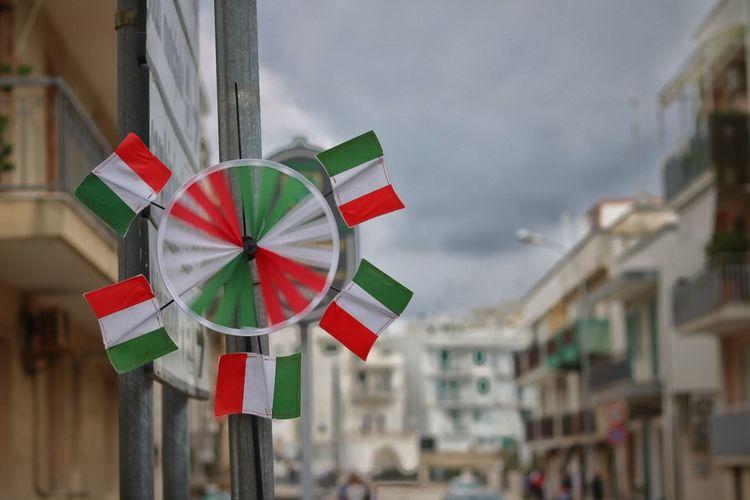 Italian flag pinwheel toy on pole in city
