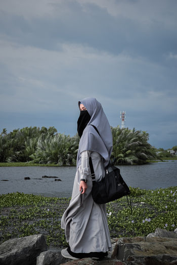 Man standing on shore against sky