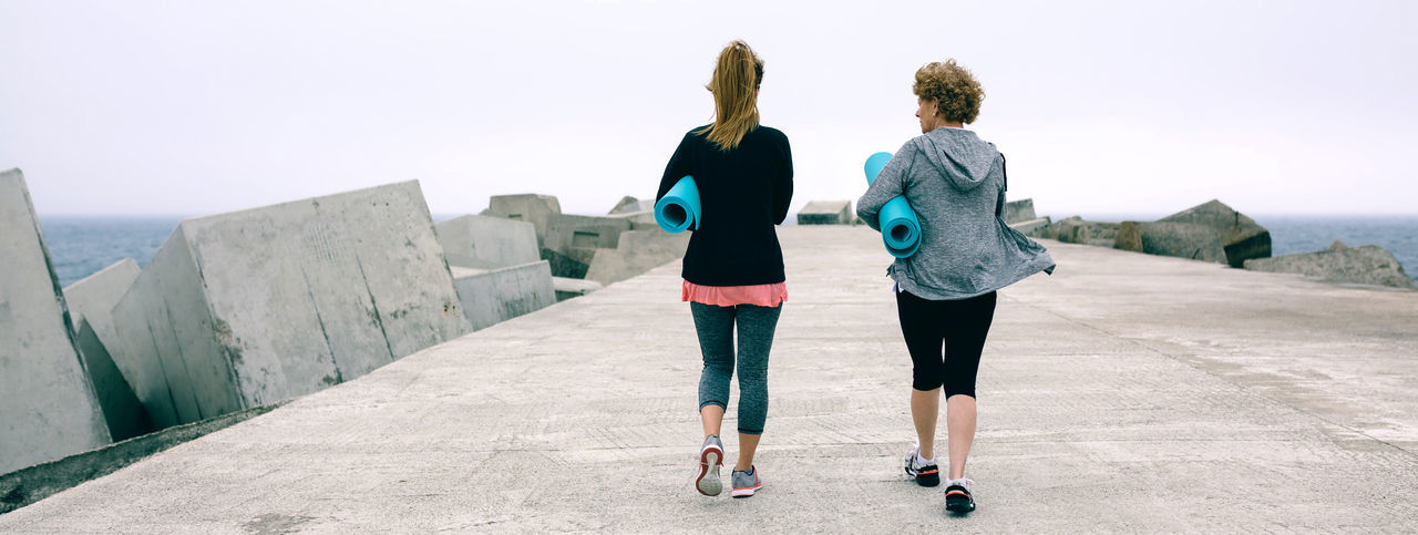 Back view of two unrecognizable women walking outdoors by sea pier Aged Elderly Exercise Mat Walking Unrecognizable People Two People Lifestyle Workout Fitness Sportswear Activity Panorama Panoramic Web Banner Freedom Healthy Lifestyle Training Sport Pier Sea Water Outdoors Female Woman