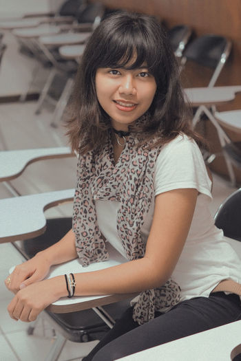 Portrait Of Smiling Young Woman Sitting In Classroom