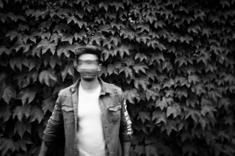 Blurred motion of young man standing against ivy in park