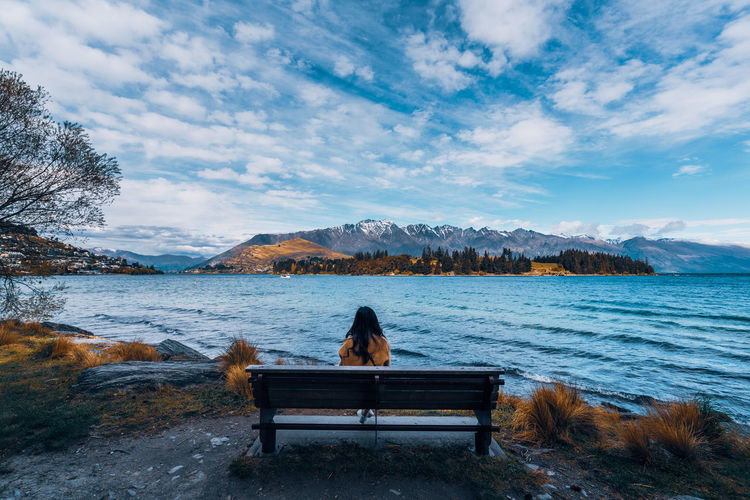 Rear view of people sitting on bench by lake against sky