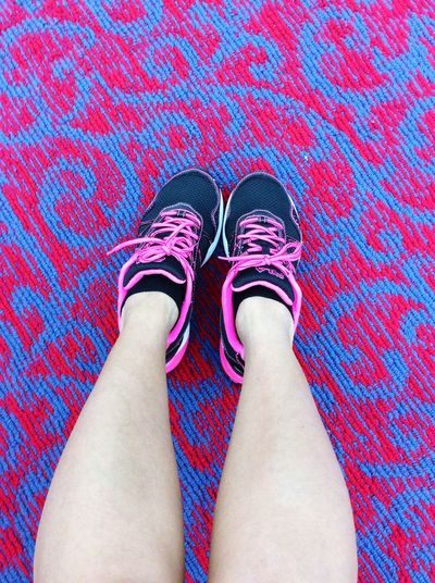 Directly Above View Of Woman With Sports Shoes On Textured Carpet